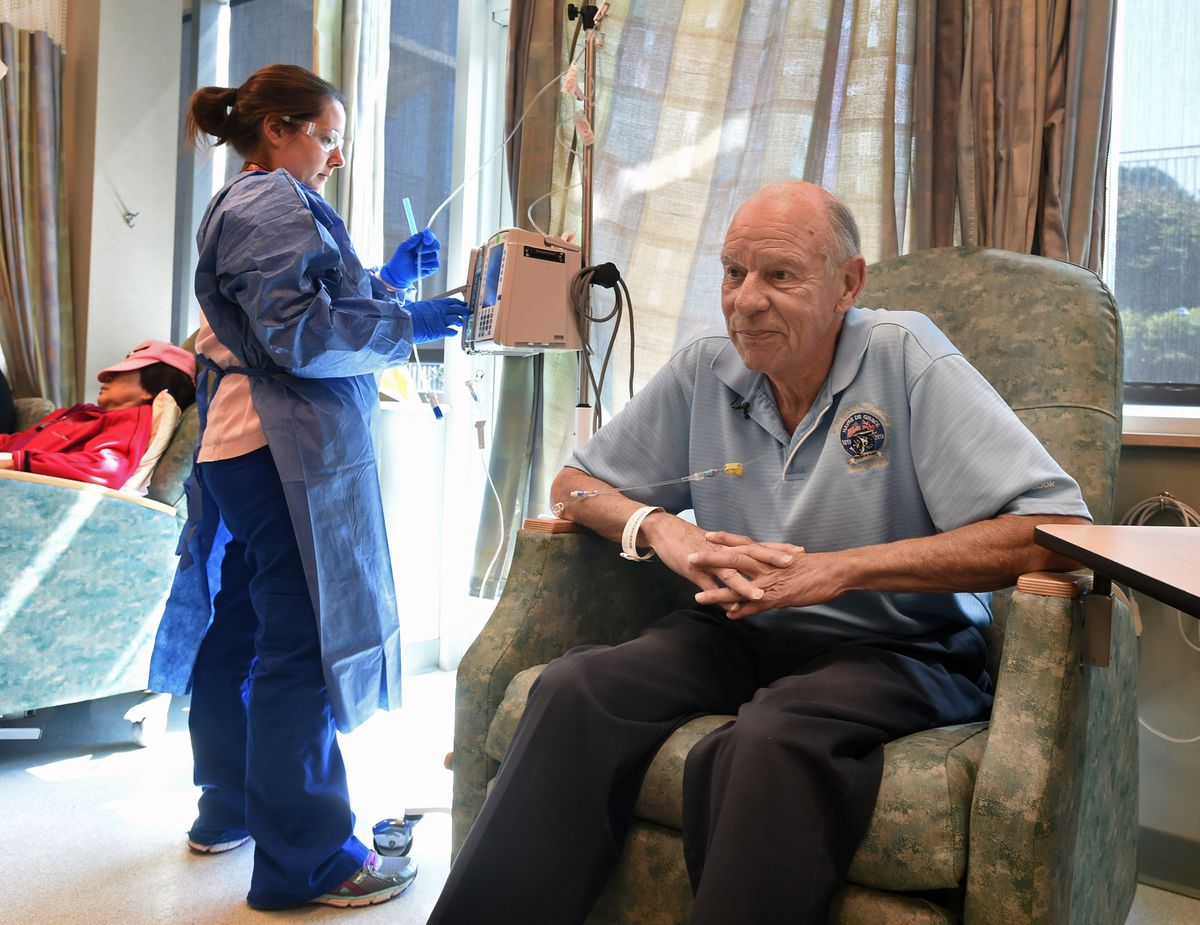 """Cancer patient Williard """"Neal"""" Mills, 67, right, of Havre de Grace, waits as nurse Erin Choi set up his biweekly immunotherapy treatment at the Harry & Jeannette Weinberg Cancer Center at Franklin Square Hospital. (Kenneth K. Lam/Baltimore Sun/TNS file)"""
