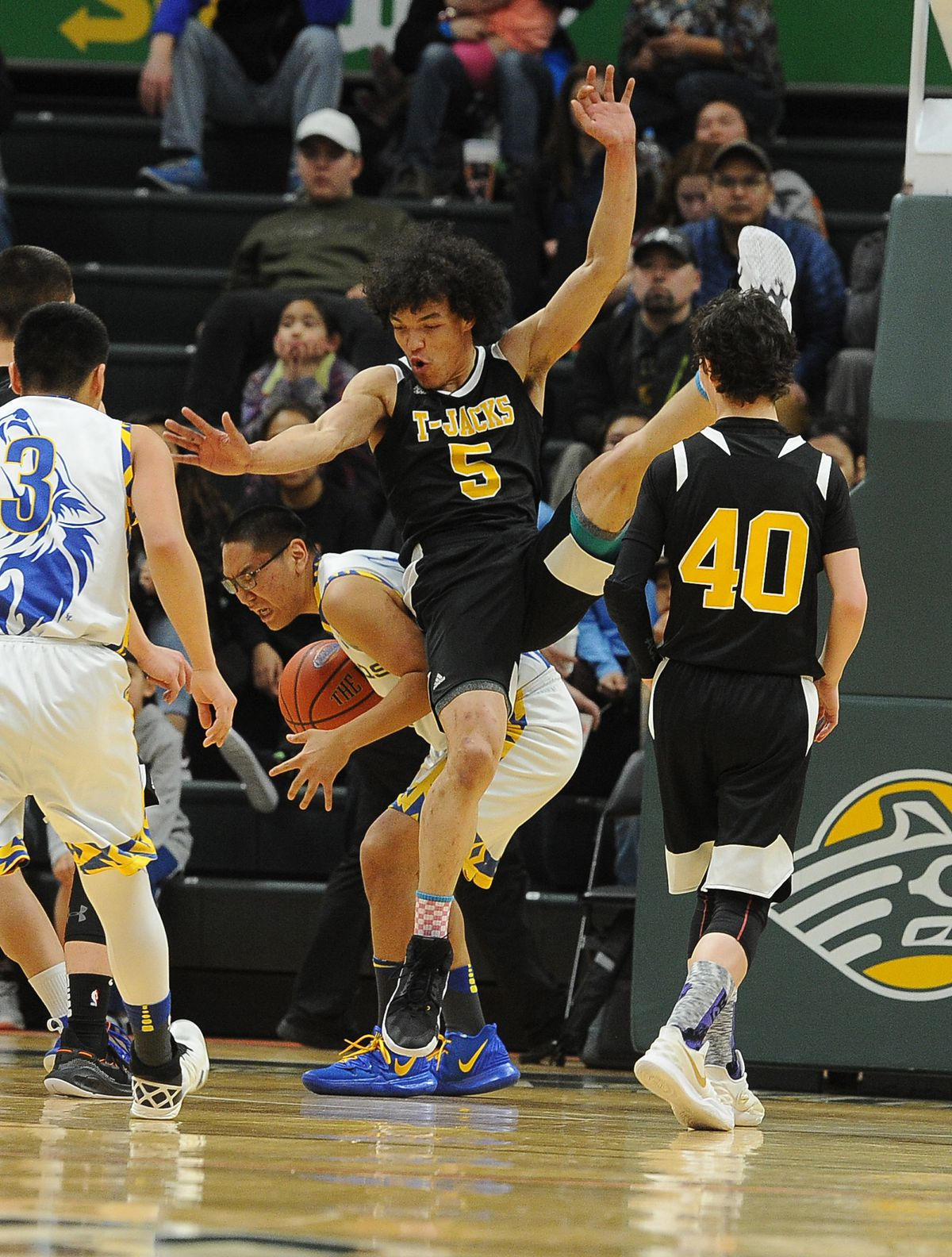 King Cove's Jason Durate comes down on top of Nunamuit's Jacob Ahgook in the Class 1A boys state basketball championship game at the Alaska Airlines Center on Saturday, March 16, 2019. King Cove defeated Nunamuit 59-54. (Photo by Bob Hallinen)