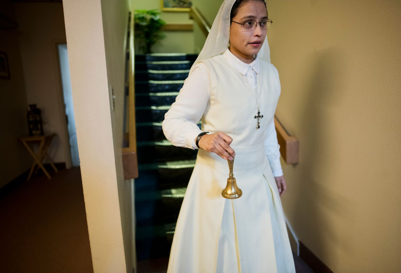 Carmen Sanchez, a postulant or candidate to become a nun, rings a bell to call the Sisters of Adoration to prayers on March 26, 2018. (Marc Lester / ADN)