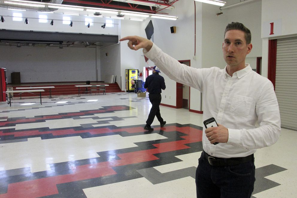This June 14, 2019, photo shows Jeremy Price, a deputy chief of staff to Alaska Gov. Mike Dunleavy, showing reporters the cafeteria at Wasilla Middle School in Wasilla that would be available to lawmakers for the special session. (AP Photo/Mark Thiessen)