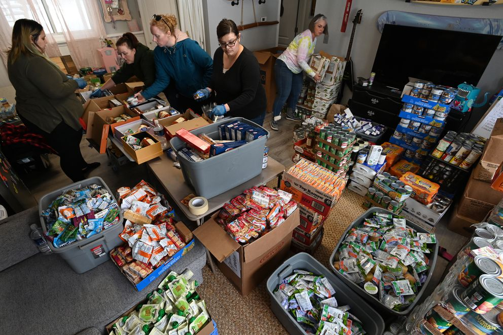 Star Behind the Stripes, a group of JBER military wives, assembled hundreds of pantry boxes for the Children's Lunchbox program operated by Bean's Cafe, in an Eagle River home on Wednesday, March 18, 2020. (Bill Roth / ADN)