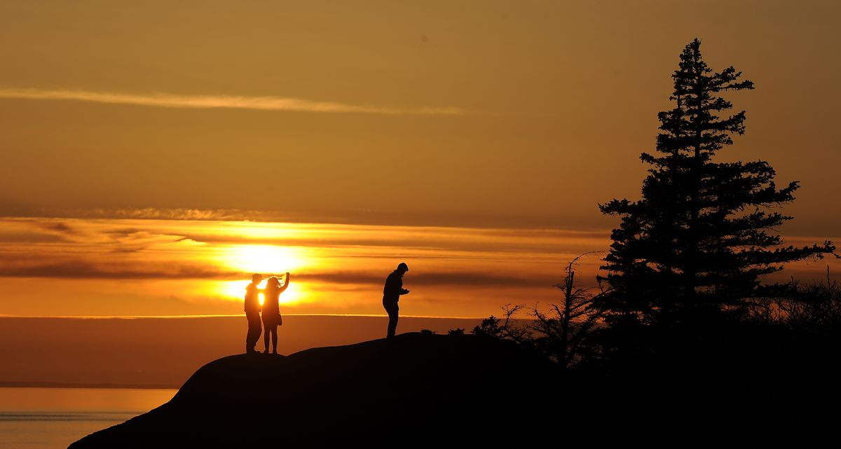 People enjoy the sunset at Beluga Point south of Anchorage on Thursday, March 26, 2019. (Photo by Bob Hallinen)