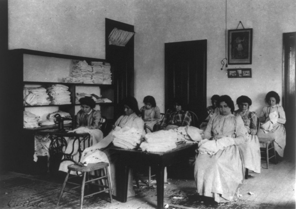 Native American girls attend a clothes-mending class at the school in 1901. (Photo by Frances Benjamin Johnston courtesy of the Library of Congress)