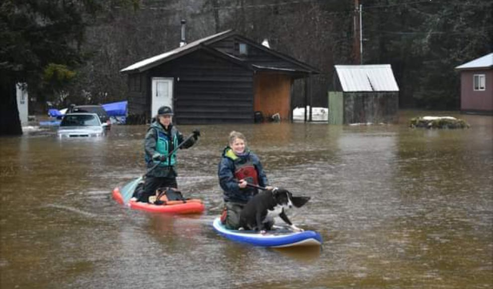 On stand-up paddleboards, Kaitlyn Tolin, left, and Amanda Painter rescue their friend's 9-year-old dog, Molly, from her flooded home in Spruce Grove Trailer Park in Haines on Thursday, Dec. 3, 2020. (Angie Goodwin)