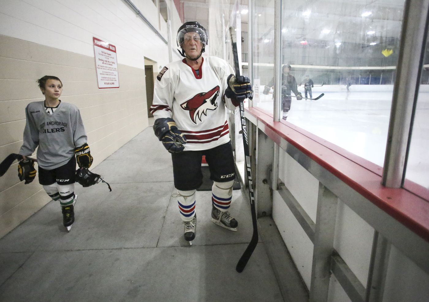 Jimmy Reese, 82, prepares to head out onto the ice as a young player walks past. (Emily Mesner / ADN)