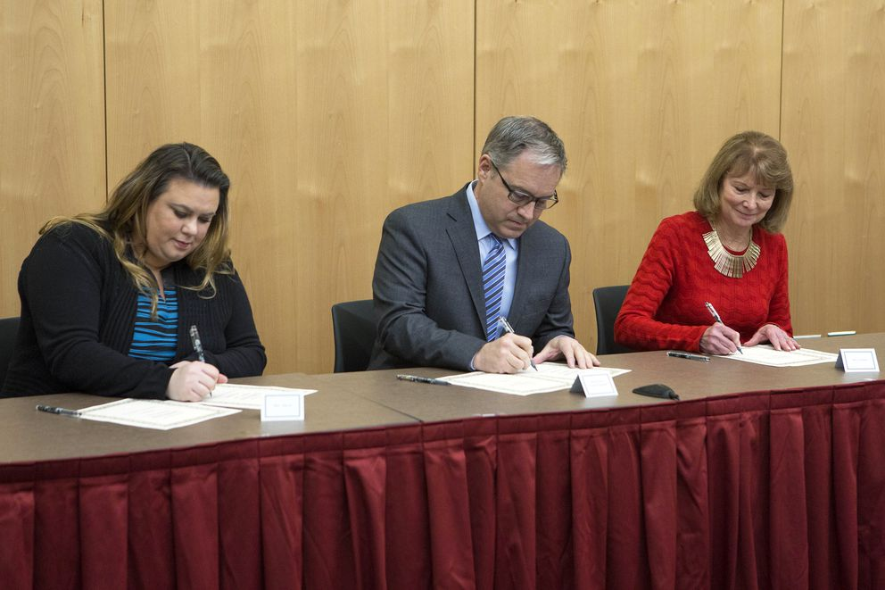 State of Alaska Electors from left Jacqueline Tupou of Juneau, former Gov. Sean Parnell of Anchorage and Carolyn Leman of Anchorage sign documents to cast votes in the Electoral College for President-Elect Donald Trump and Vice Pres. Mike Pence during a ceremony at the Alaska State Museum on Monday, Dec. 19, 2016 in Juneau. (Brian Wallace)