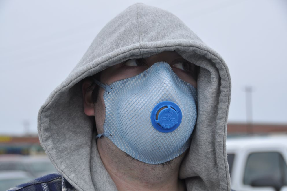 Joshua Hammer wore a protective mask as he waited to cross the Seward Highway in Midtown Anchorage as ash from Redoubt volcano falls on Anchorage on March 28, 2009. (Bob Hallinen / ADN archive)
