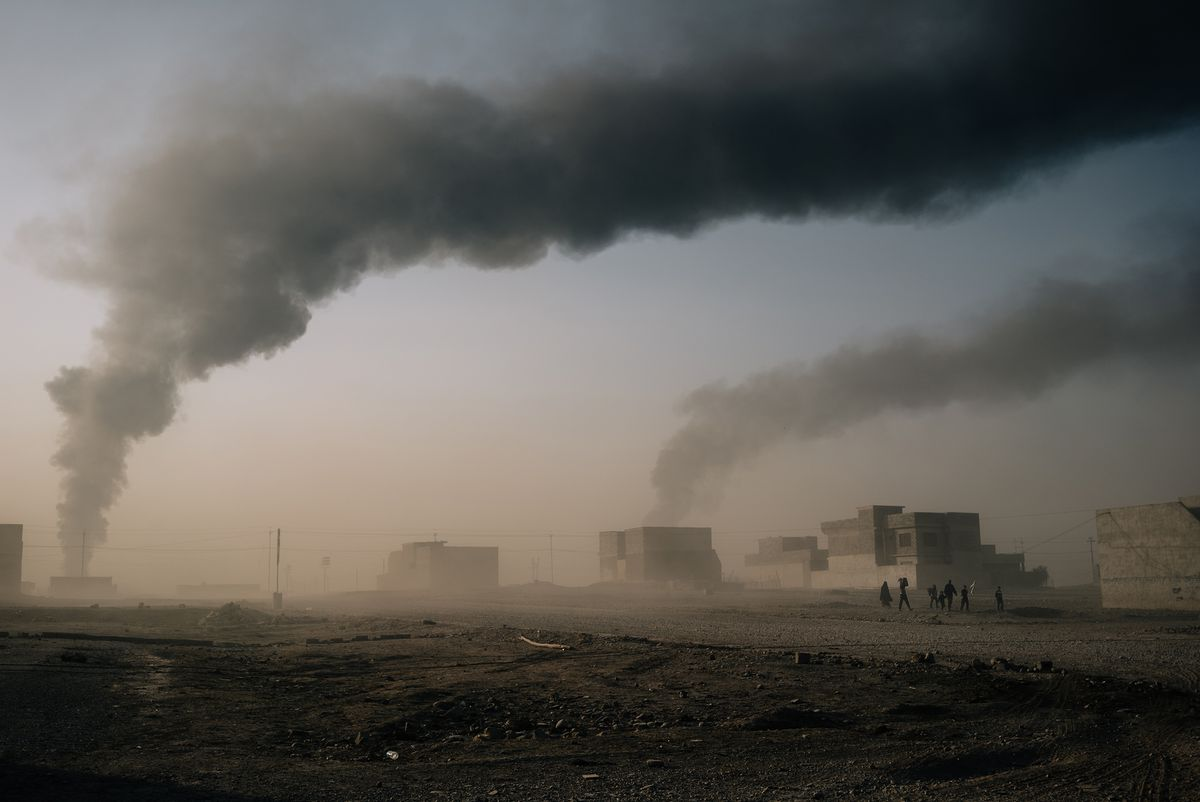 Civilians, carrying a white flag and a few belongings, seek to escape fighting between Islamic State militants and Iraqi security forces in the city of Mosul. (Photo for The Washington Post by Alice Martins)