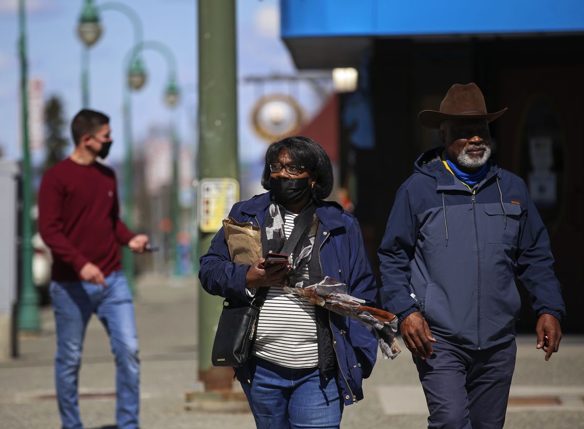 Rosa and Harold Meadors, visiting from Seattle, cross West Fourth Avenue in downtown Anchorage on Thursday, May 13, 2021. (Emily Mesner / ADN)