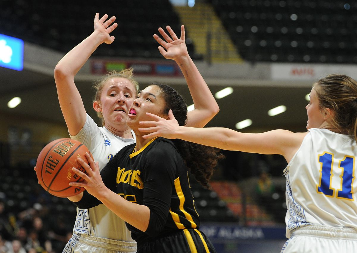 King Cove's Jalaya Durate, center, drives to the basket as Tri-Valley's Rachel Cockman, left, and Jazmyn Byfuglien defend in the Class 1A girls state basketball championship game Saturday. (Photo by Bob Hallinen)
