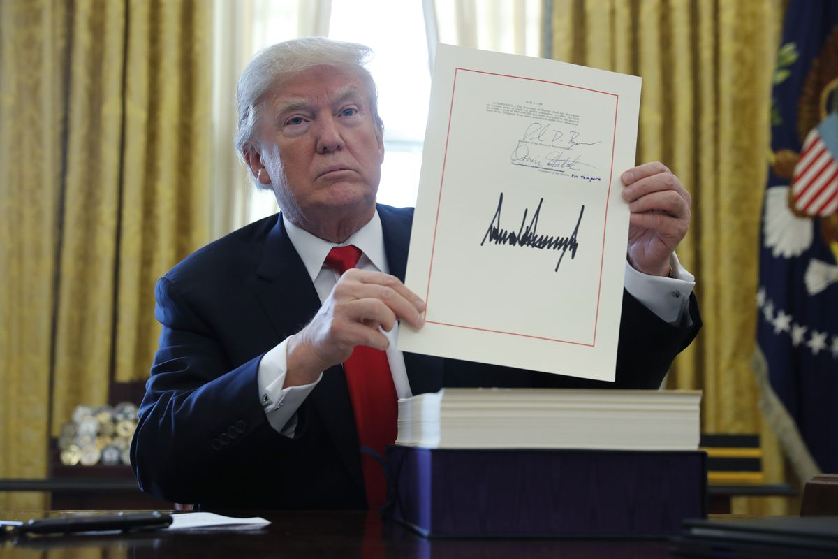 President Donald Trump displays his signature after signing the $1.5 trillion tax bill along with a short-term government spending bill in the Oval Office of the White House on December 22, 2017.(REUTERS/Jonathan Ernst)