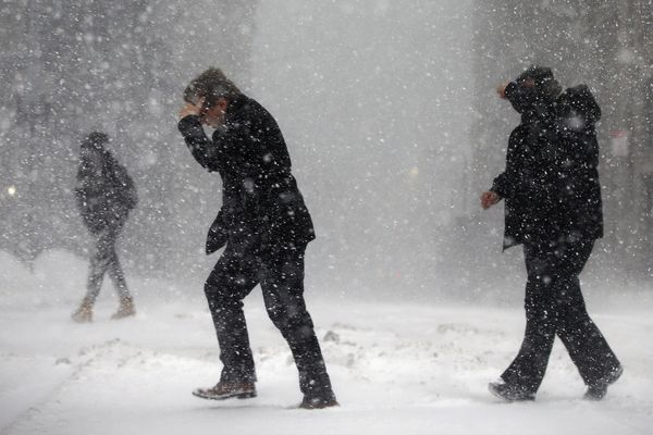Pedestrians cross the street in downtown Boston, Thursday, Jan. 4, 2018. A massive winter storm swept from the Carolinas to Maine on Thursday, dumping snow along the coast and bringing strong winds that will usher in possible record-breaking cold. (AP Photo/Michael Dwyer)