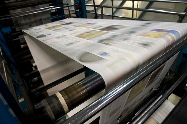Newsprint rolls through the press. Pressmen, inserters and other staff produced the print edition of the Alaska Dispatch News for the last time at the press facility on Northway Drive late Oct. 14 and early Oct. 15, 2017. The press had been the production center for the Anchorage Daily News, and in recent years Alaska Dispatch News, since the 1980s. (Marc Lester / Alaska Dispatch News)