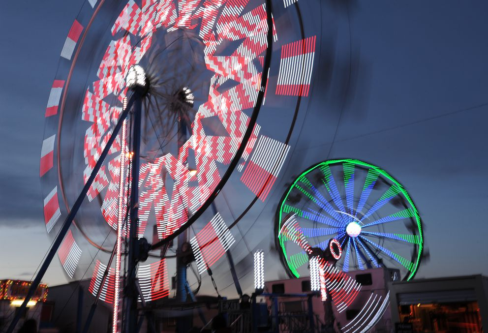 Blurred lights on the Eli and Century ferris wheels as people enjoyed the Golden Wheel Amusements rides at the Rondy Carnival during the Anchorage Fur Rendezvous winter festival on Monday night, Feb. 27, 2017. (Bill Roth/Alaska Dispatch News)​