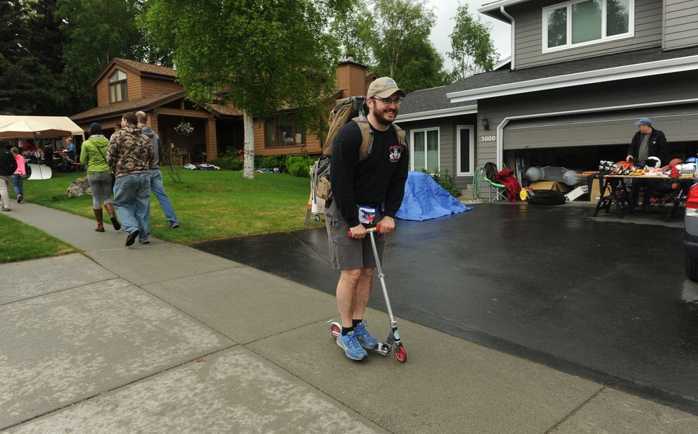 Chris Schnieder rides the scooter he bought for 3$ at the Kempton Hills neighborhood garage sale on Saturday, May 21, 2016. Schnieder said 'why walk when you can ride.' (Bob Hallinen / Alaska Dispatch News)