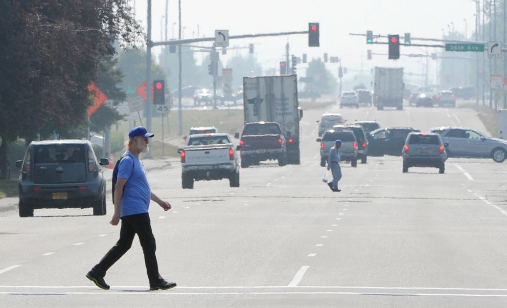 Pedestrians cross C Street as smoke from the 92,657 acres, or about 144 square mile Swan Lake wildfire on the Kenai Peninsula has settled in Anchorage reducing the visibly and lowering the air quality to an 'unhealthy ' level on Sunday, July 7, 2019. (Bill Roth / ADN)