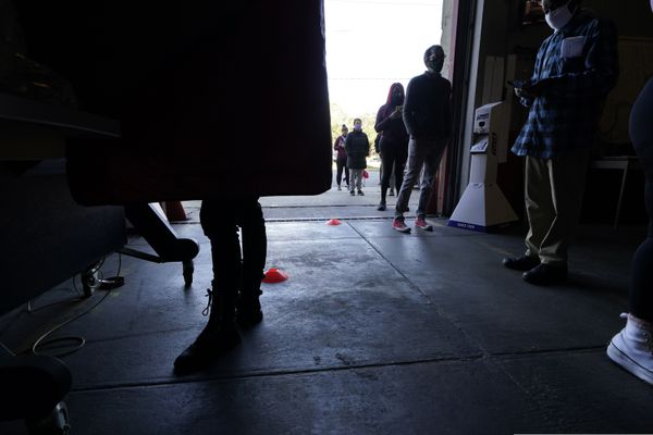 A voter casts her ballot while others wait in line to vote on Election Day, in the Mid City section of New Orleans, Tuesday, Nov. 3, 2020. (AP Photo/Gerald Herbert)
