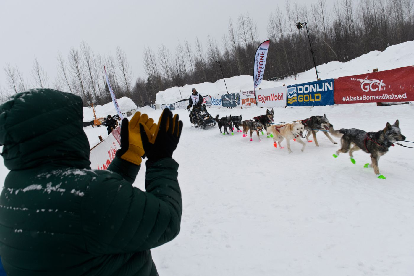 Veteran Iditarod musher and current Mat-Su Borough mayor Vern Halter applauds as Jeff Deeter reaches the finish line of the 2021 Iditarod Trail Sled Dog Race on March 15, 2021. (Marc Lester / ADN)