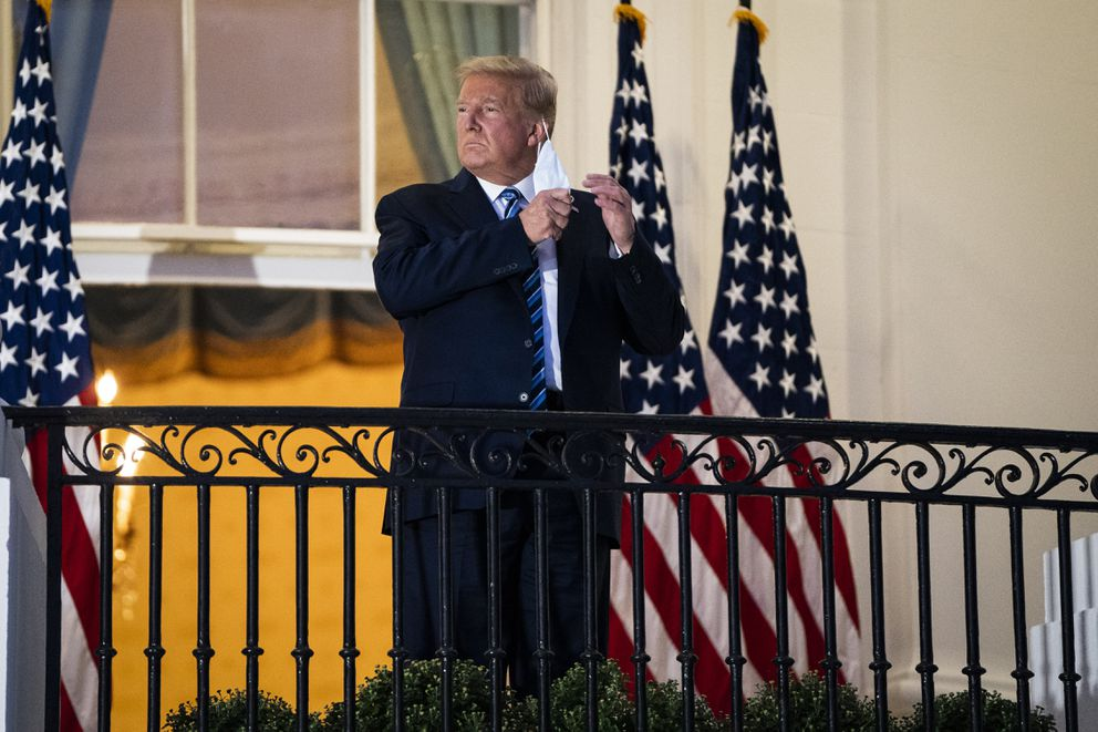 President Trump takes off his mask as he salutes Marine One from the White House balcony on Oct. 5, upon his return home after receiving treatment for covid-19 at Walter Reed National Military Medical Center. (Washington Post photo by Jabin Botsford.)