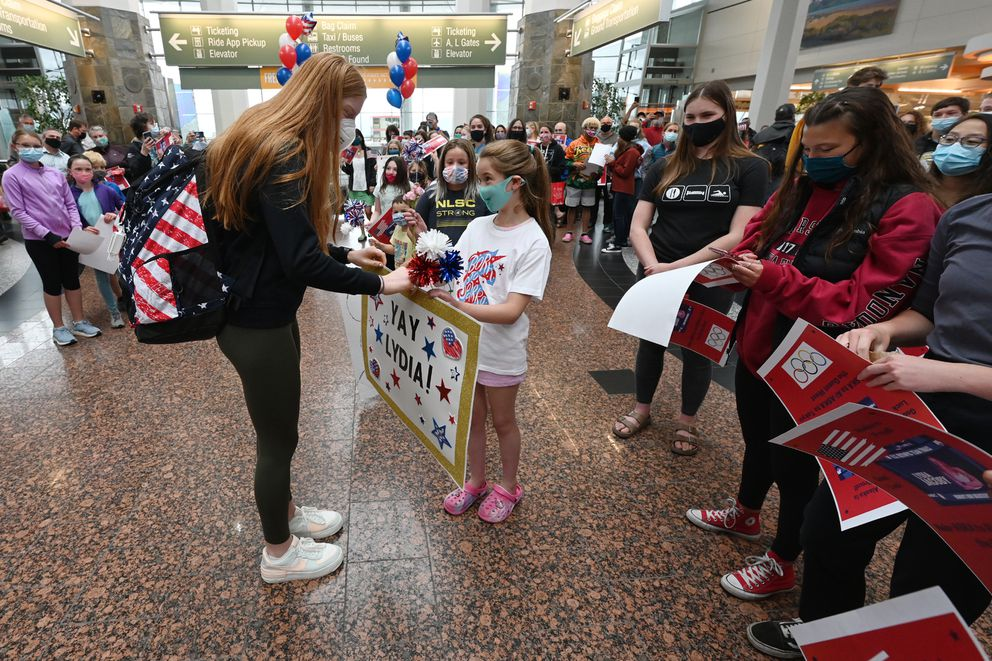 Swimmer Lydia Jacoby is greeted by fans at Ted Stevens Anchorage International Airport last month after returning from the U.S. Olympic swim trials. (Bill Roth / ADN)