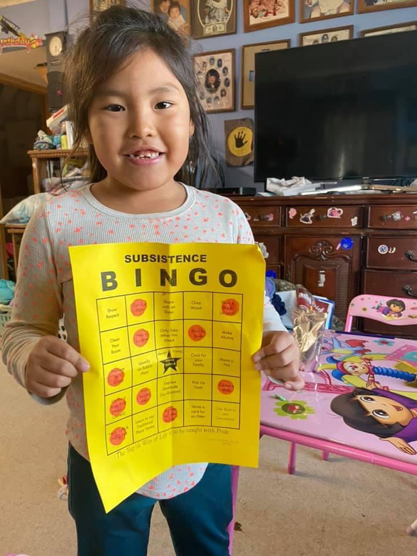 A student displays her completed subsistence bingo card.