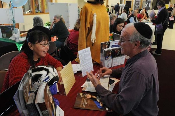Connie Irrigoo of the Alaska Native Heritage Center welcomes a contribution from Rabbi Michael Oblath during a Mitzvah Mall at Congregation Beth Sholom Dec. 5, 2010. The alternative gift fair featured nonprofit agencies selling