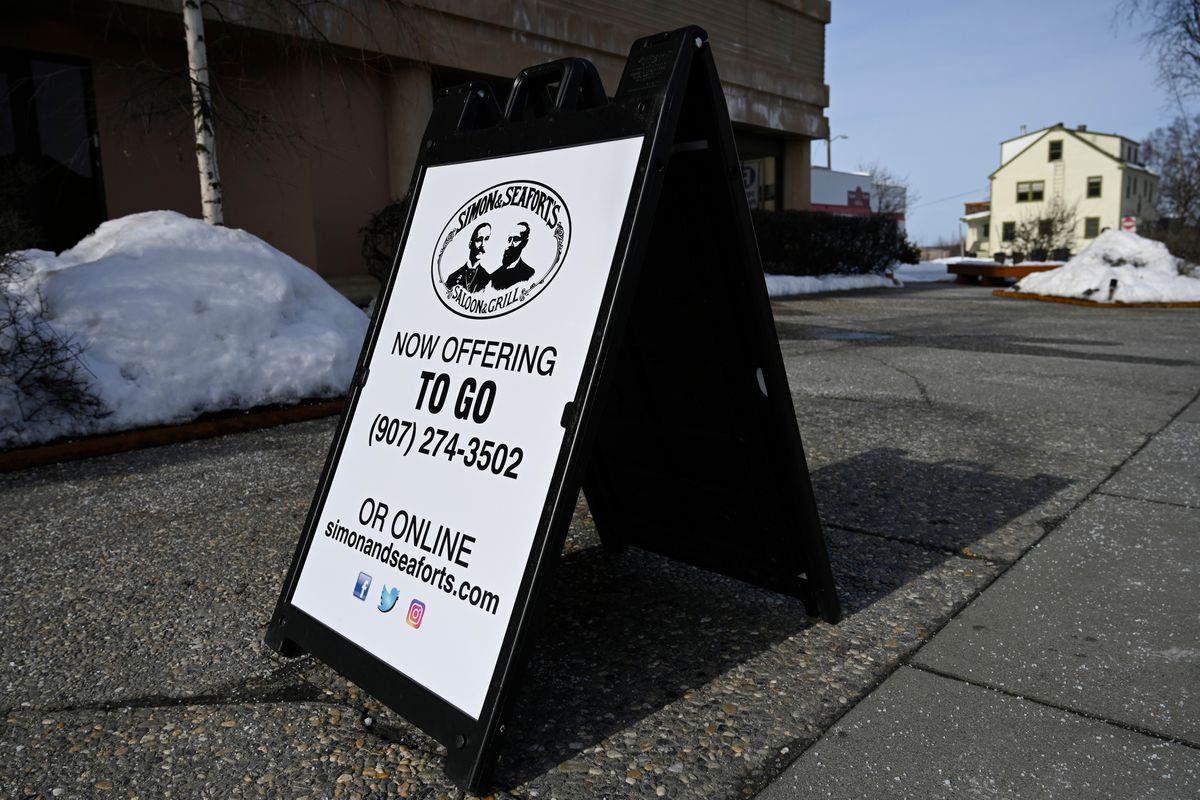 A sign on L Street in downtown Anchorage advertises to-go meals for Simon and Seafort's Saloon and Grill on March 20, 2020. (Marc Lester / ADN)