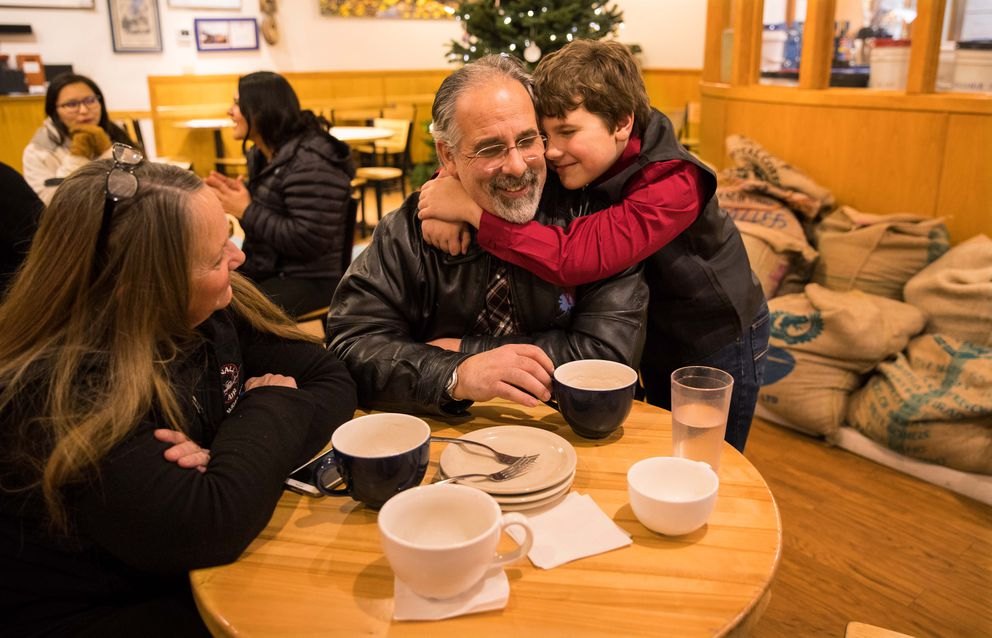Loretta Fogg, left, and her husband Matt Anderson, center, spend time with their son, Aidan Fogg Anderson at a coffee shop in Fairbanks on Dec. 5. Both parents are pilots for small airlines that fly in Alaska. (Ruth Fremson/The New York Times)