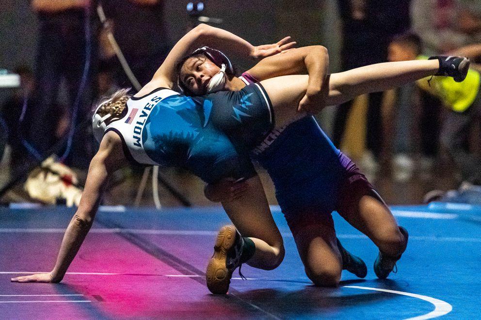 East's Jamiezon Garcia lifts Eagle River's AJ Pennington in the girls 103-pounds finals. Garcia won the match. (Loren Holmes / ADN)