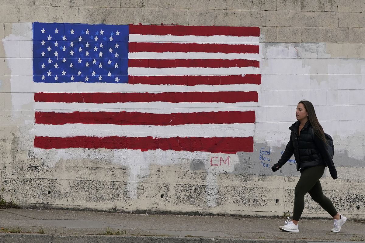 FILE - In this May 13, 2021, file photo, pedestrian walks in front of an American flag painted on a wall during the coronavirus outbreak in San Francisco. A number of states immediately embraced new guidelines from the CDC that say fully vaccinated people no longer need to wear masks indoors or out in most situations. But other states - and some businesses _ are taking a wait-and-see attitude. (AP Photo/Jeff Chiu, File)