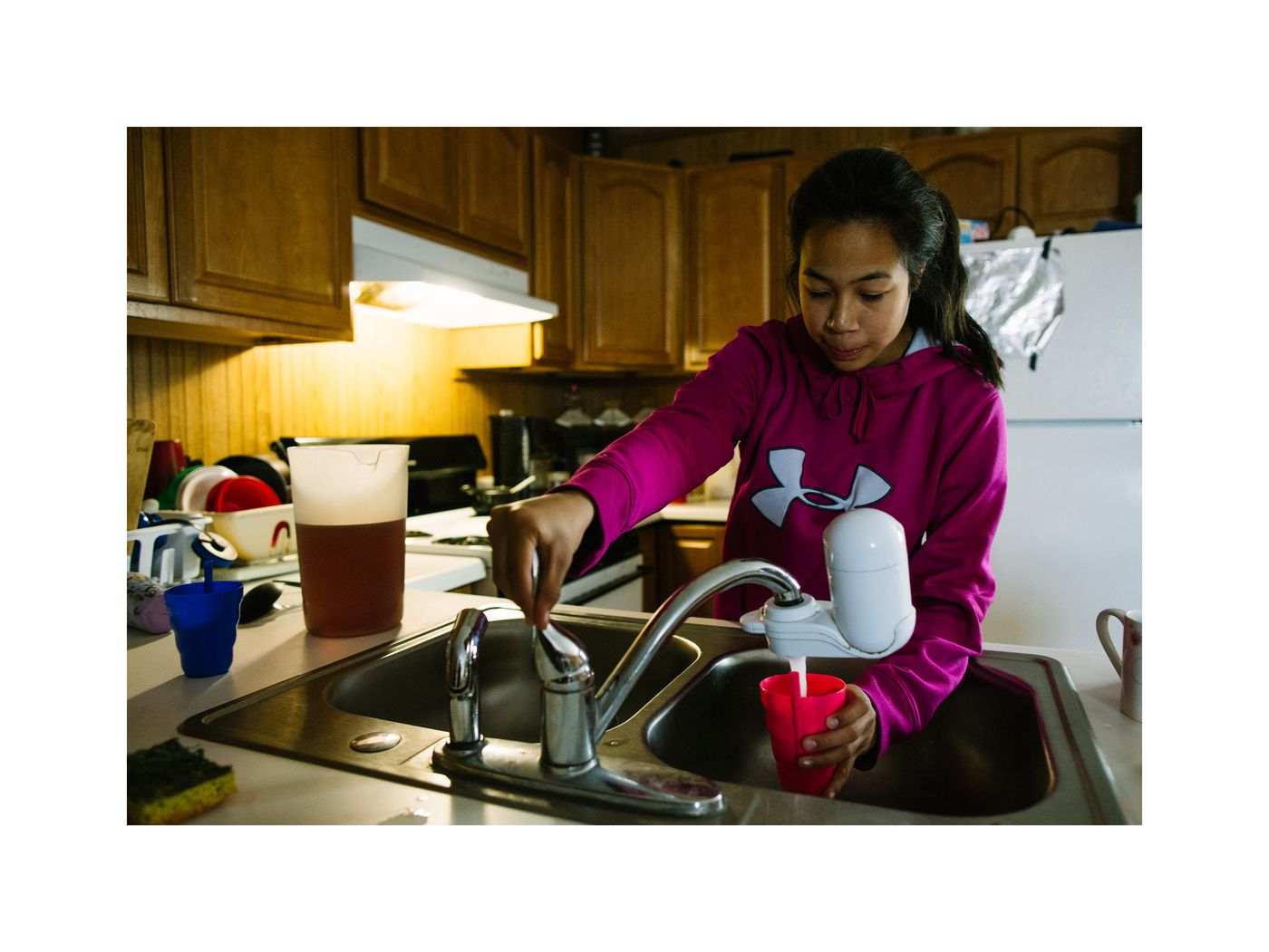Zoya Ayaan using the newly installed kitchen sink with running water. (Photo by Kerry Tasker)