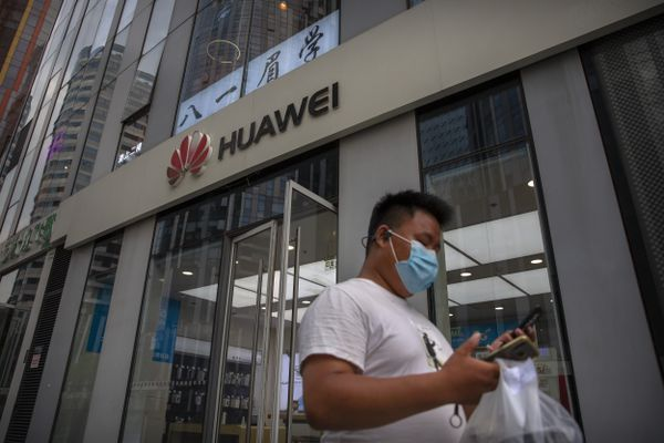 FILE - In this Wednesday, July 1, 2020 file photo, a man wearing a face mask to protect against the new coronavirus looks at his smartphone as he walks past a Huawei store in Beijing. The British government is reportedly poised to backtrack on plans to give Chinese telecommunications giant Huawei a limited role in the U.K.'s new high-speed mobile phone network, a decision with broad implications for relations between the two countries. Britain's decision to re-examine the question, the results of which will be announced Tuesday, July 14 came after the U.S. threatened to sever an intelligence-sharing arrangement because of concerns Huawei equipment could allow the Beijing government to infiltrate U.K. networks. (AP Photo/Mark Schiefelbein, file)