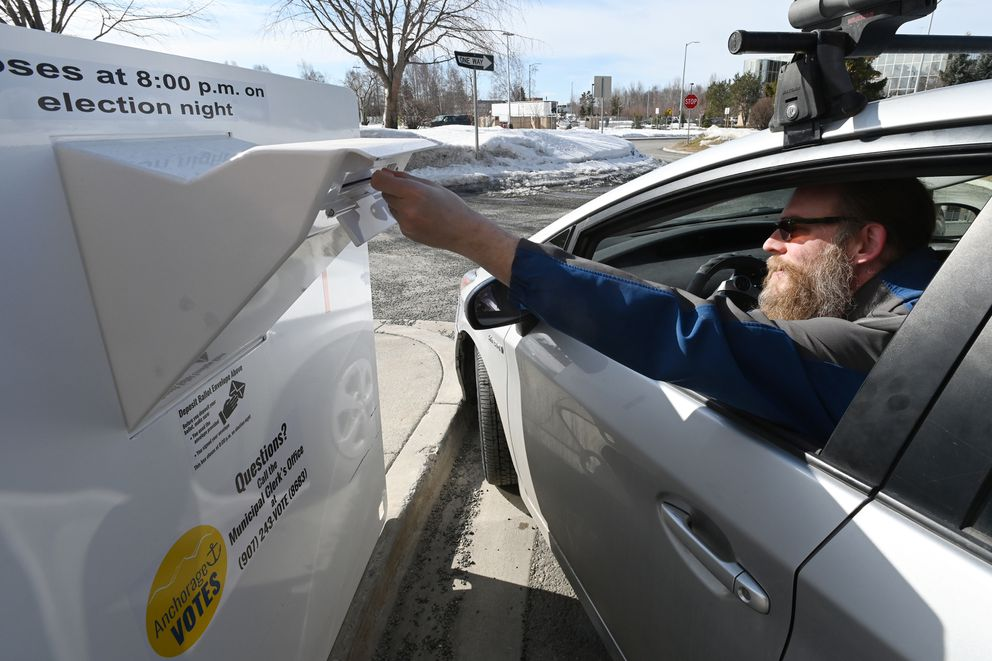 Bryan Talbott-Clark places a ballot in a secure Vote-By-Mail Ballot Drop Box at the Loussac Library on Monday, April 6, 2020. Tuesday is Election Day for the Regular Municipal Election. (Bill Roth / ADN)