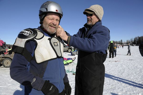 RETRANSMISSION TO CORRECT AGE TO 78 - FILE - In this March 6, 2016, file photo, Iditarod Trail Sled Dog Race veteran Jim Lanier gets help with protection from handler George McCann prior to the race in Willow, Alaska. Iditarod officials confirm in an email to The Associated Press they are not allowing 78-year-old musher Jim Lanier to race in 2020. Iditarod officials say they based their decision on observations the race marshal and judges made when Lanier scratched in 2018. (AP Photo/Michael Dinneen, File)