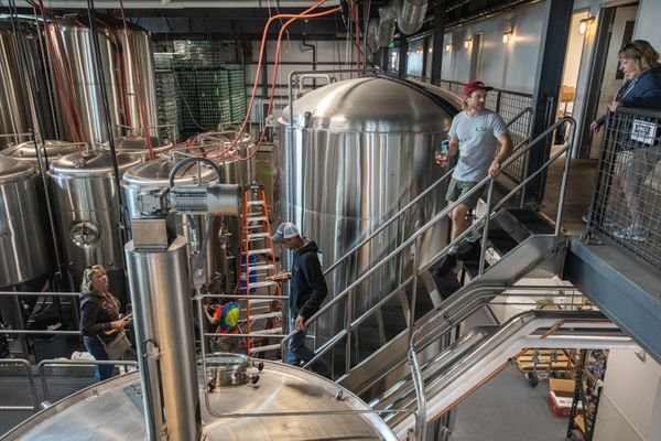 King Street head brewer Maxwell Crutch, in red hat, leads a tour of the brewery Thursday, Aug. 29, 2019. The tour is operated by Big Swig Tours, which takes patrons on tours of breweries, which would not be possible under proposed state regulations. (Loren Holmes / ADN)