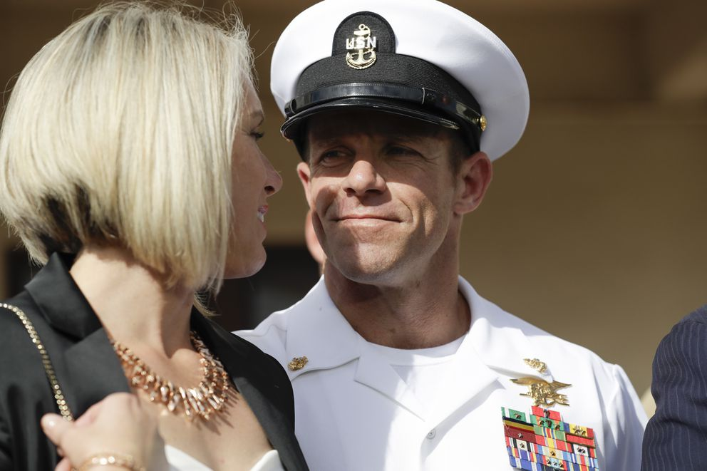 Navy Special Operations Chief Edward Gallagher, right, walks with his wife, Andrea Gallagher as they leave a military court on Naval Base San Diego, Tuesday, July 2, 2019, in San Diego. A military jury acquitted the decorated Navy SEAL of murder in the killing of a wounded Islamic State captive under his care in Iraq in 2017. (AP Photo/Gregory Bull)
