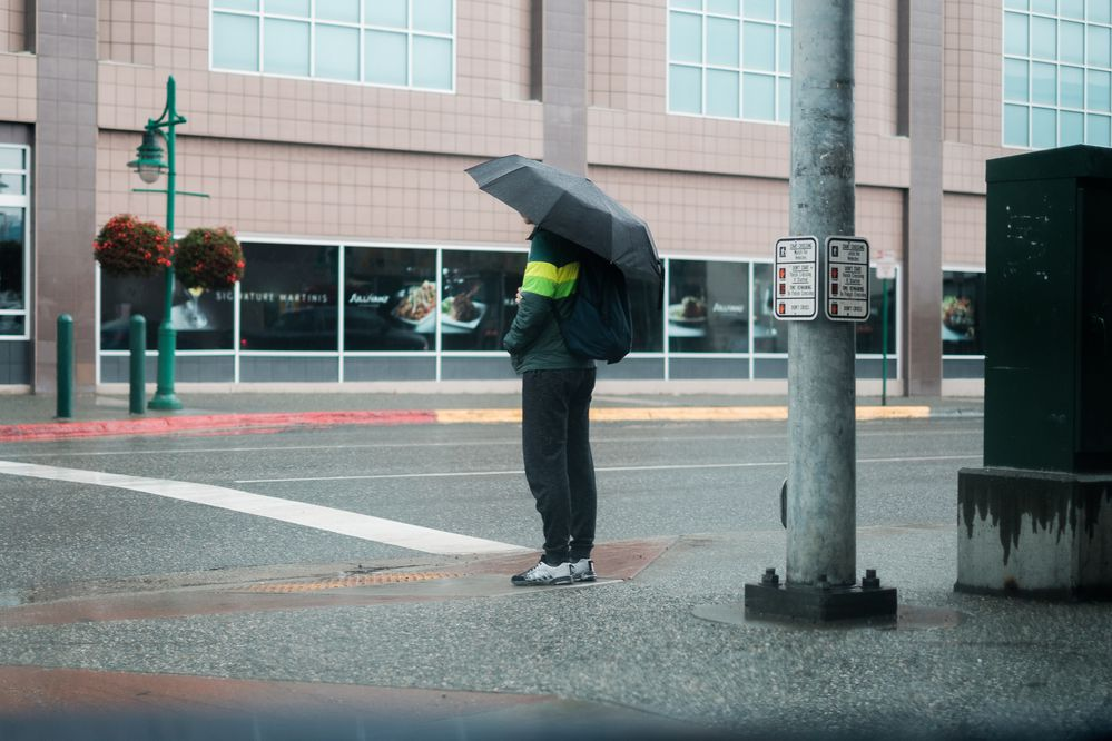 A pedestrian uses an umbrella to shield themself from the rain as they wait for the traffic signal to change on August 16, 2017. (Young Kim / Alaska Dispatch News)