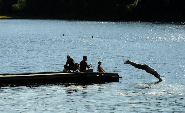 A swimmer dives off the dock past a family fishing at Little Campbell Lake. (Bob Hallinen / ADN)
