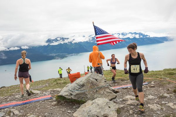Lauren Spinelli runs around the flag at the top of the mountain in the women's race on Mount Marathon in Seward, July 4, 2017. (Loren Holmes / ADN)
