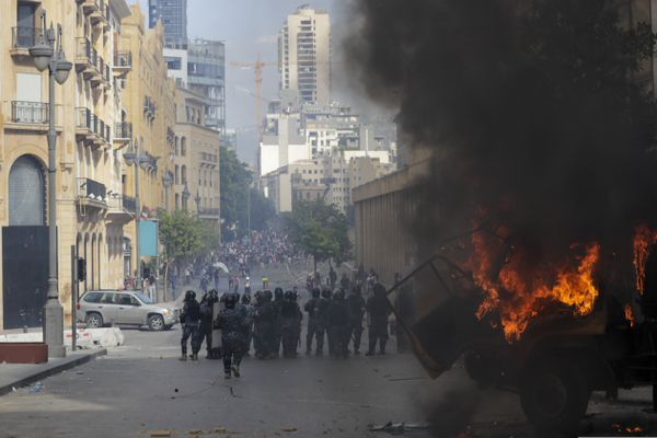 People clash with police during a protest against the political elites and the government after this week's deadly explosion at Beirut port which devastated large parts of the capital and killed more than 150 people, in Beirut, Lebanon, Saturday, Aug. 8, 2020. (AP Photo/Hassan Ammar)