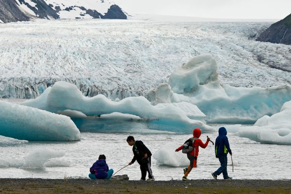 Kids explore the waterline at Spencer Lake with a good view of Spencer Glacier and some of its icebergs. Hikers can access the area, south of Portage in Chugach National Forest, by way of Alaska Railroad's whistle stop service, which drops passengers about a 1.3-mile walk from the lake. (Marc Lester / ADN archive)