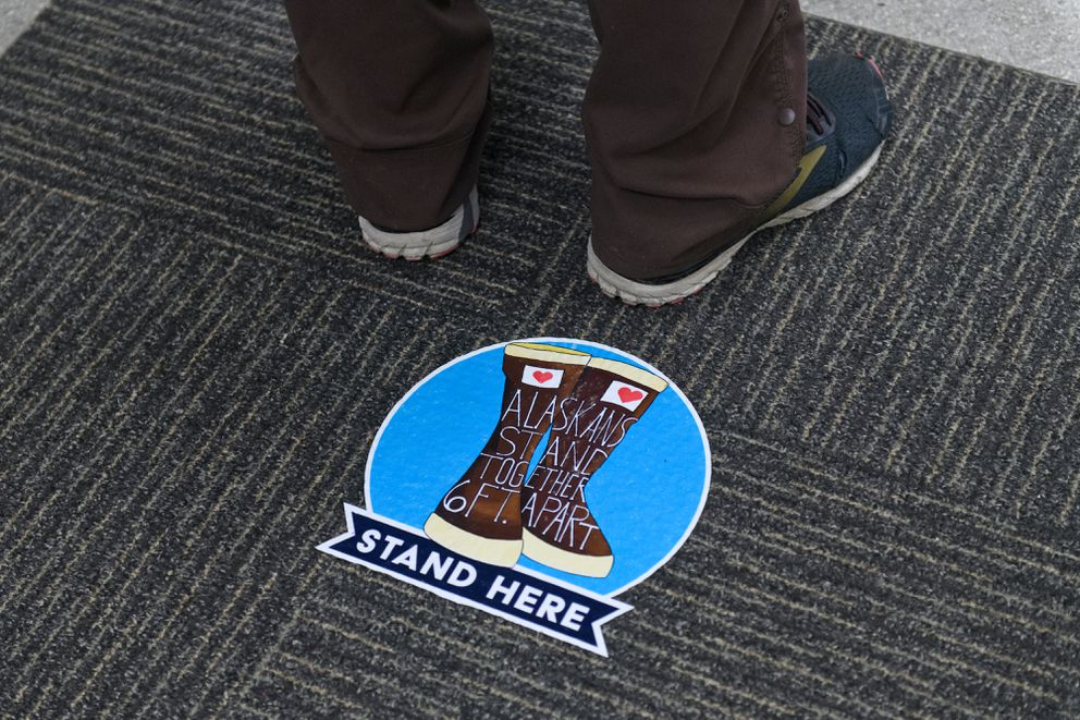 A sticker on the floor encourages social distancing outside the early voting location at the Midtown Mall. (Marc Lester / ADN)