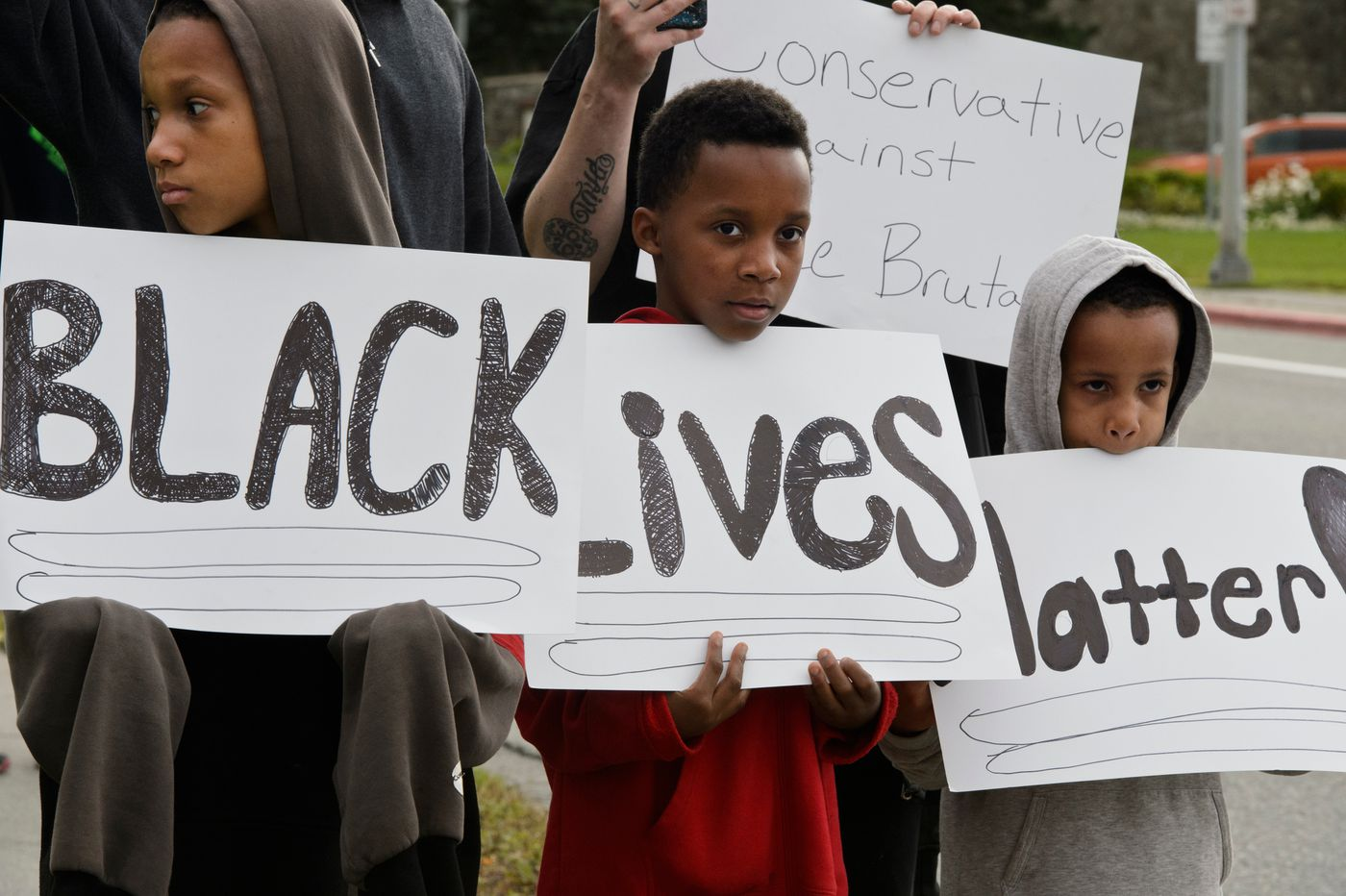From left, Kurt, Semaj and Amir Wright hold signs that read Black Lives Matter. (Marc Lester / ADN)