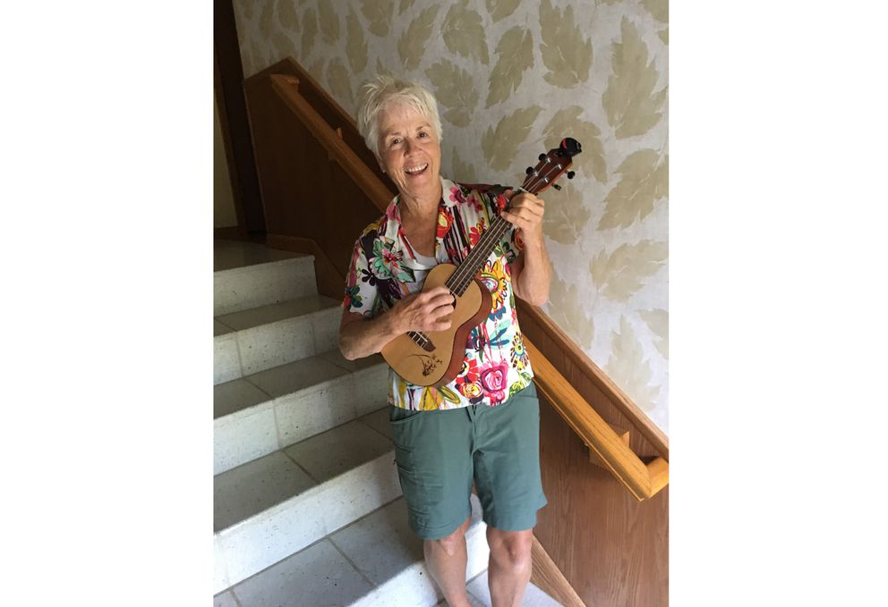 """In this undated photo, Pat Adamson-Waitley, 62, poses with her ukulele at her home in Edina, Minn. Adamson-Waitley had played the ukulele a handful of times, but in March, she said, """"I started playing it every day."""" (Jane Adamson-Waitley via AP)"""