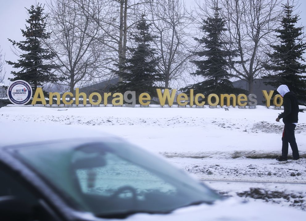 A person walks by a sign welcoming people into Anchorage along E. Fifth Avenue on Friday, Feb. 26, 2021. (Emily Mesner / ADN)