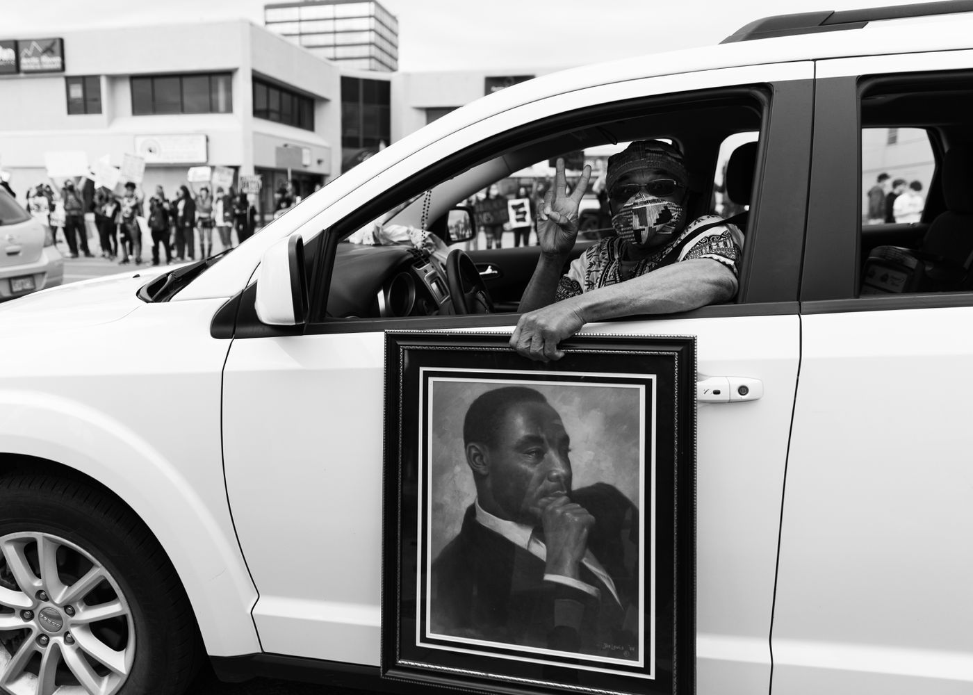Photograph by Jovell Rennie, 2020 Cal Williams holding a portrait of Martin Luther King Jr. at a Black Lives Matter protest, Anchorage, 2020