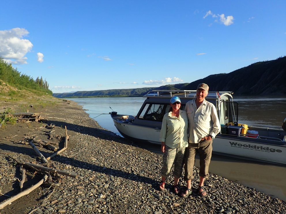 Chris Florian and her husband Skip Ambrose on the Yukon River across from cliffs where peregrine falcons nest. (Photo by Ned Rozell)