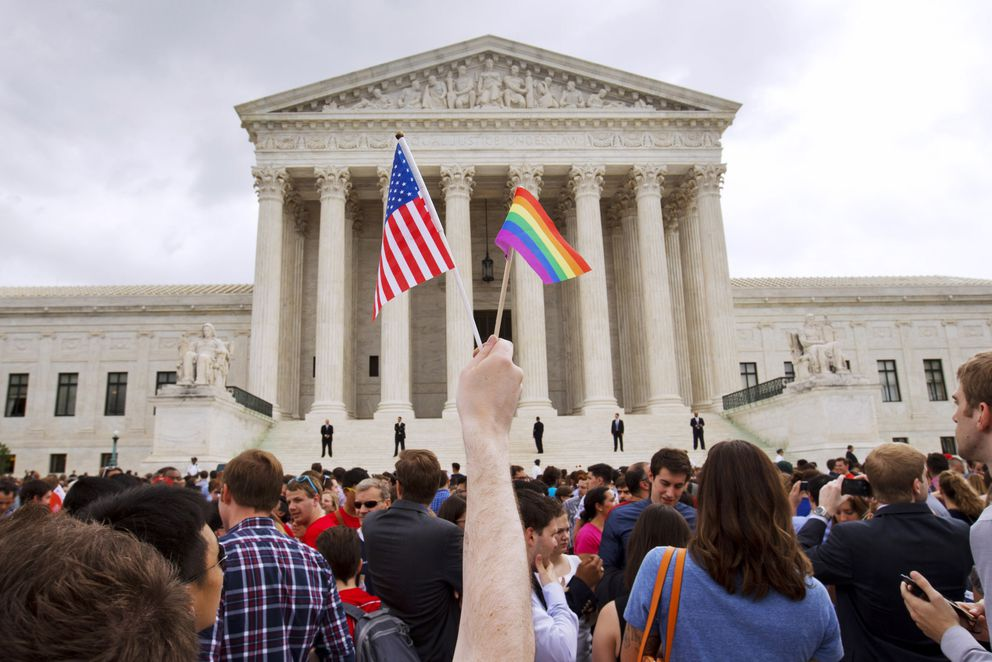 In this June 26, 2015 file photo, a man holds a U.S. and a rainbow flag outside the Supreme Court in Washington after the court legalized gay marriage nationwide. Court documents show the state of Alaska for years maintained a discriminatory policy that denied some same-sex spouses benefits by wrongly claiming gay marriage was not recognized in Alaska, long after courts ordered they be recognized. (AP Photo/Jacquelyn Martin, File)