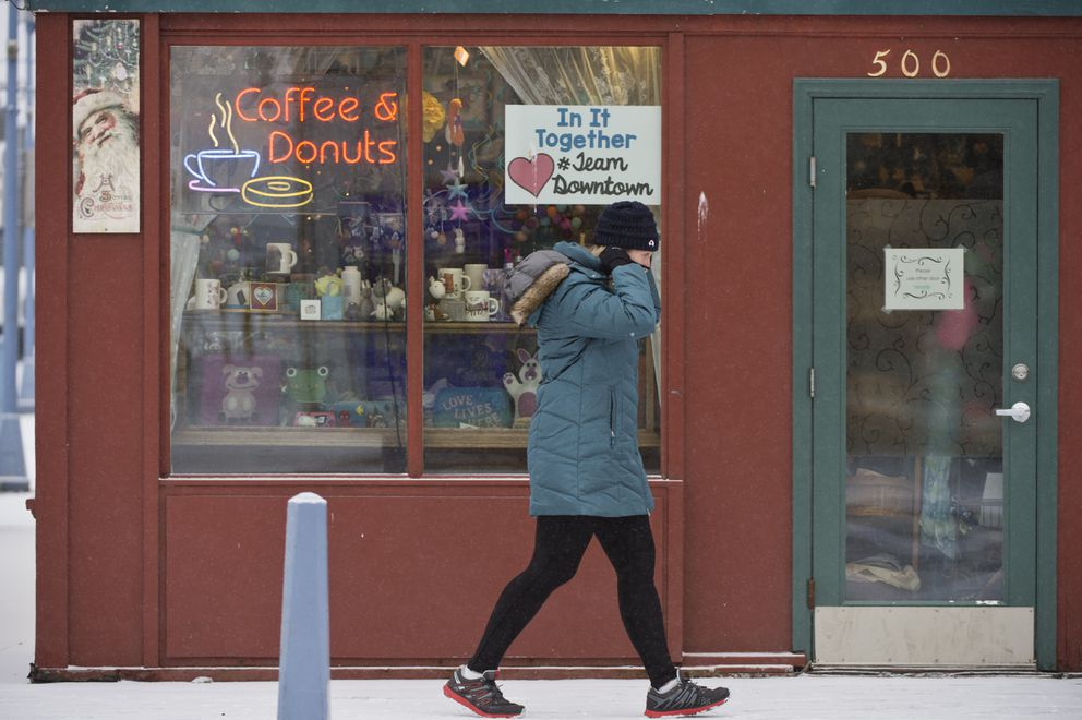 A person puts on a mask before entering Kobuk Coffee Co. in downtown Anchorage on November 6, 2020. (Marc Lester / ADN)