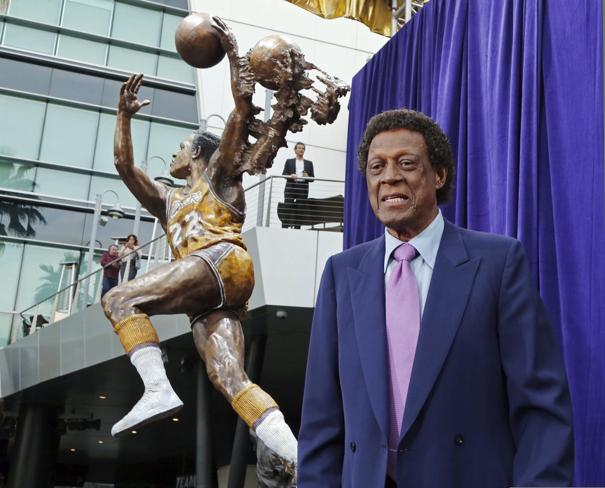FILE - Elgin Baylor stands next to a statue, just unveiled, honoring the Minneapolis and Los Angeles Lakers great, outside Staples Center in Los Angeles, in this Friday, April 6, 2018, file photo. Elgin Baylor, the Lakers' 11-time NBA All-Star, died Monday, March 22, 2021, of natural causes. He was 86. The Lakers announced that Baylor died in Los Angeles with his wife, Elaine, and daughter Krystal by his side. (AP Photo/Reed Saxon, File)